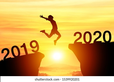 Silhouette sport woman jump through the gap between hill to the new year of 2019 to 2020 on sunset orange sky. happy New year concept.