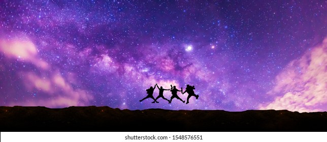 Silhouette tourists Jumping up in the sky with Panorama blue night sky milky way and star on dark background.Universe filled with stars, nebula and galaxy with noise and grain.select focus