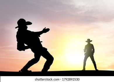Silhouette of two cowboy gunslinger engaged in a shootout at sunset.