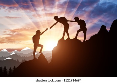 Silhouette of two female mountaineers helping another female mountaineer to overcome the obstacle in the mountains. Conceptual scene of helping the climber