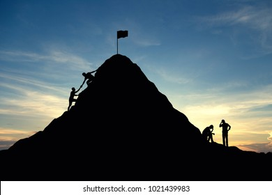 Silhouette two group young man, The first group is helping each other achieve success. Another group is thinking about how to do it.  Business, successful, achievement, teamwork and goal concept