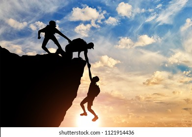 Silhouette of two male climbers rescuing another male climber pulling his arm. Conceptual scene of teamwork of climbers