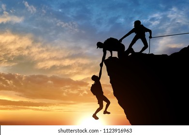 Silhouette of two male climbers rescuing another male climber pulling his arm. Conceptual scene climbers help