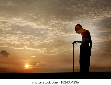 Silhouette of a vulnerable old man strolling into the sunset with a walking stick for the concept of old age. Double exposure illustration.