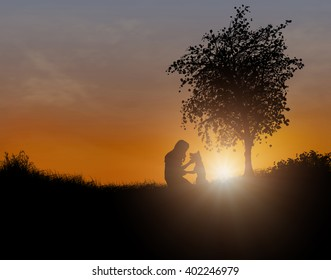 Silhouette of a woman and dog together under a tree in an open field at sunset or sunrise