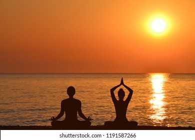 Silhouette of woman and man practicing yoga on the beach at sunrise