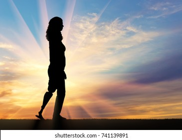 A silhouette of a woman with a prosthetic leg going up on the slope. The concept of rehabilitation of people with prosthetic legs