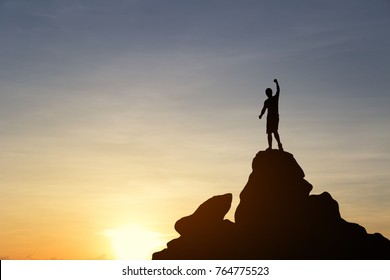 Silhouette of a young man and arm up on top mountain at sunset. Business, achievement, success, concept. Vintage filter.