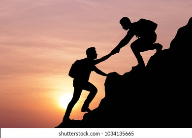 Silhouette of young man helping each other hike up a mountain at sunrise. Business, teamwork, goal, success and help concept.