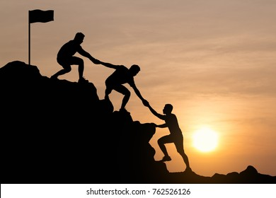 Silhouette of young man helping each other hike up a mountain, Sky and sunset background. Business teamwork success help concept. Vintage filter.