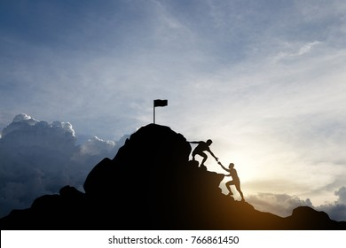 Silhouette of young man helping each other hike up a mountain, Sky and sunset background. Business teamwork success concept. Vintage filter.