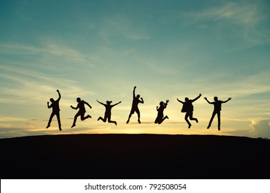 Silhouette of young man and woman jumping to celebrate success on top of hill, sky and sun light background. Vintage filter. Business, successful, happy, teamwork and goal concept.