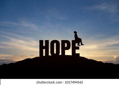 "Silhouette of young man and the word ""hope"" on mountain over sky and sunset background. business, successful, achievement and goal concept."