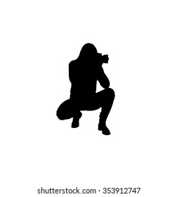 A silhouette of young woman in pants and short boots holding a professional digital camera in both hands while posing as if she were tracking a subject.