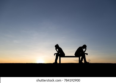 Silhouettes of couple man and woman broken heart. In nature sunset background. Love concept.