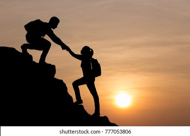 Silhouettes of couple man and woman helping each other hike up a mountain at sunrise background. Business, teamwork, success, goal, education, couple, love and help concept.