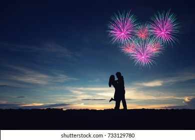Silhouettes of couple man and woman in nature sunset, fireworks background. Vintage filter. Couple of love concept.