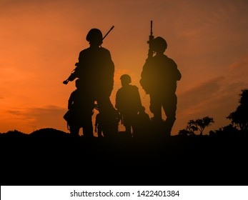Silhouettes of several soldiers with rifles against a sunset sky background