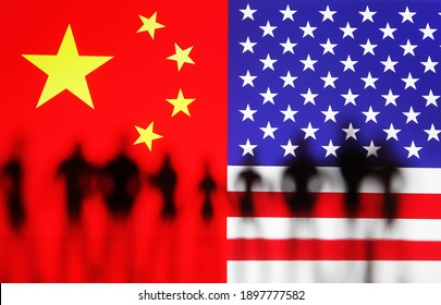 Silhouettes of small toy people in front of flags of the US and China on background.