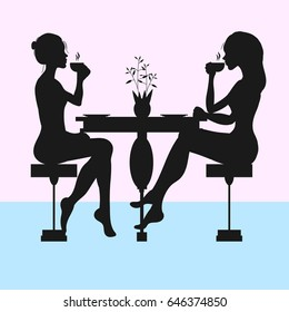 Silhouettes of two women drinking tea or coffee
