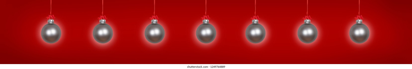 Silver hanging christmas baubles on red background
