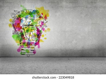 Sketch of light bulb and business ideas on cement wall