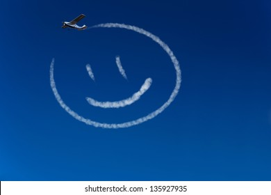 Skywriter airplane paints a happy smiley in the blue sky