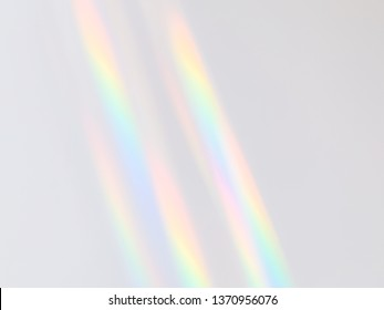 Slanted diagonal rainbow light rays on an even solid plain background.