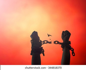 Slavery concept: Silhouette human hands raising and broken with bird flying chains at sunset