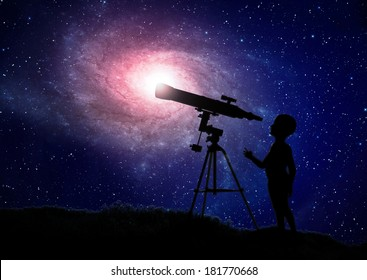 Small boy looking through a telescope