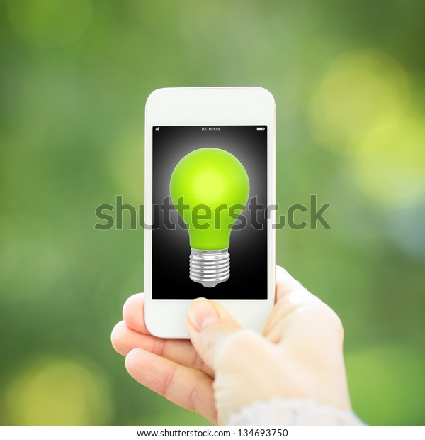 Smart phone with light bulb in hand against green spring background. Ecology concept