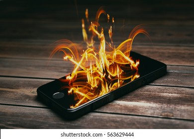Smartphone burning on wooden table. Burning smartphone with bad battery exploded or overloaded processor - 3D illustration.