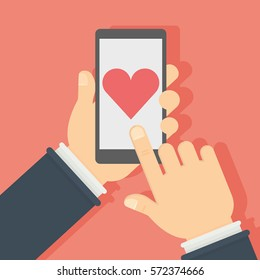 Smartphone with like button. Hands holding smartphone with heart-shaped like button on the screen. Concept of social networks, sharing.