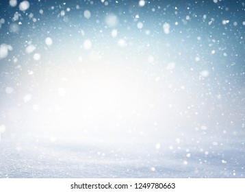 Snowflakes and snowfall exploding on a white snow covered ground and blue iced background. Winter seasonal material.
