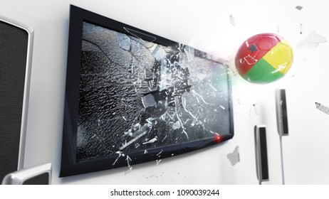 Soccer ball with the flag of Guinea-Bissau flying through a shattering tv screen.(3D rendering series)