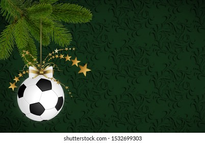 Soccer christmas bauble hanging on the fir branch. Christmas card with space for text