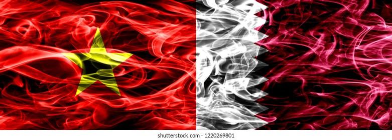 Socialist Republic of Viet Nam vs Qatar, Qatari smoke flags placed side by side. Thick colored silky smoke flags of Vietnam and Qatar, Qatari