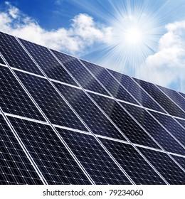 Solar energy panels in grass against sunny sky.