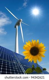 Solar panels, wind turbine and sunflower against a sunny sky
