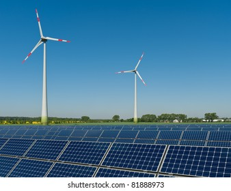 Solar panels and wind turbines against a rapeseed field