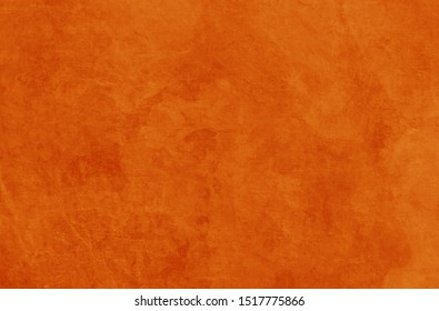 Solid orange background texture for halloween autumn fall and thanksgiving in old vintage rock or stone wall or rustic painted and distressed metal rust design