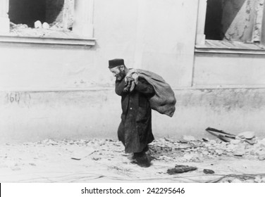 A solitary Jewish man carrying a sack walking past bomb damaged buildings in Poland in the early days of World War II. 1939-40.