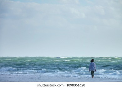 Solitary woman stands at edge of sandy beach on a barrier island, watching waves approach while others break, along the Gulf of Mexico in Florida, with digital oil-painting effect. 3D rendering.