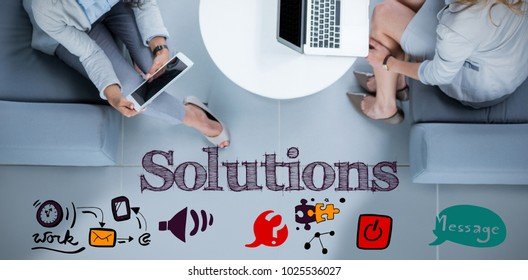 Solutions text message against businesswomen using laptop and digital tablet