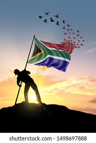 South Africa flag turn to birds while being planted by a man on a hill during sunrise.