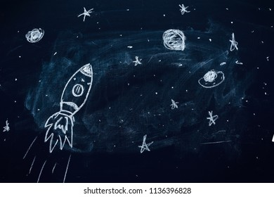 Space rocket with planets and stars doodle drawing on school chalkboard