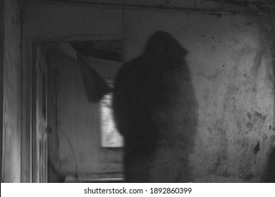 A spooky horror concept of a dark hooded figure standing by a doorway in an abandoned building. With an abstract blurred edit.