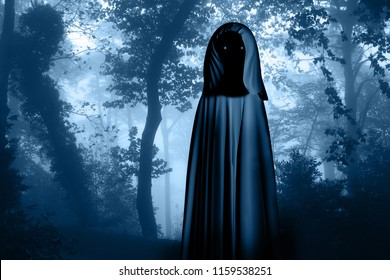 Spooky monster in hooded cloak with glowing eyes in misty forest landscape. Photo toned in blue color