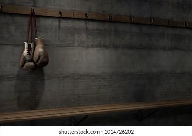 Spotlit old vintage boxing gloves hanging on a hanger above an empty wooden bench in a locker change room - 3D render