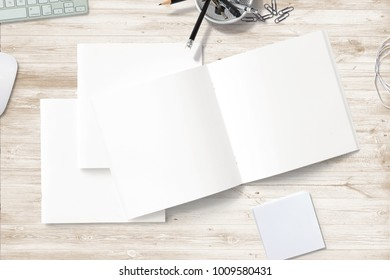 Square Magazines with blank soft cover and pages on wooden desk. 3d illustration with workplace objects for your presentation.